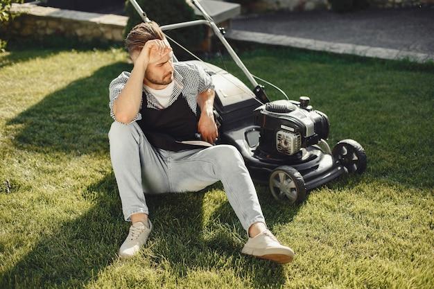 Man maaien gras met gazonverhuizer in de achtertuin. mannetje in een zwart schort. Gratis Foto