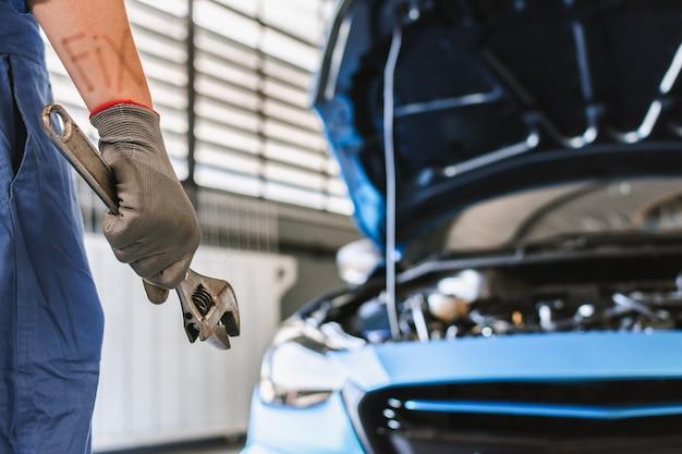 Man mechanic inspectie hold sleutel voor fix blauwe auto voor service onderhoudsverzekering Premium Foto