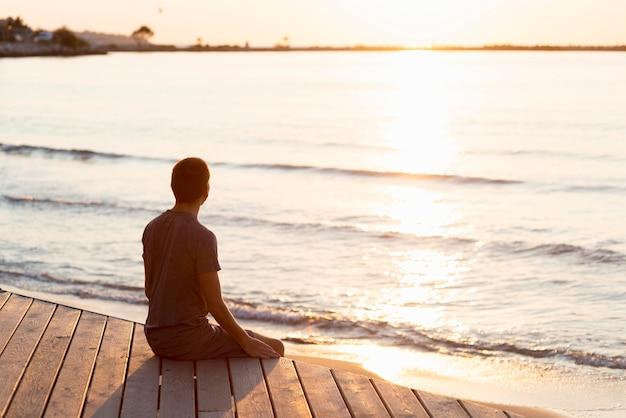 Man mediteren op het strand Gratis Foto