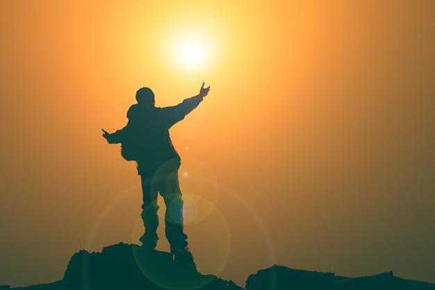 Man met armen uitgebreid naar de hemel bij zonsopgang Premium Foto