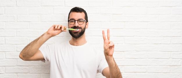 Man met baard tanden poetsen Premium Foto