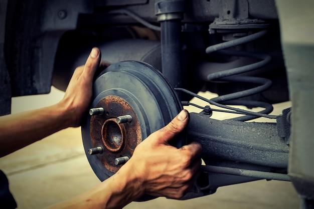 Man met behulp van automonteur blokkeer het windwiel. om uw banden en remmen voor auto te controleren. auto monteur voorbereiding voor het werk. Premium Foto