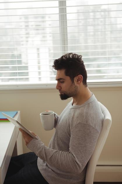 Man met behulp van digitale tablet terwijl het drinken van koffie Gratis Foto