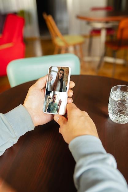 Man met behulp van mobiel voor videocall terwijl drinkwater Gratis Foto