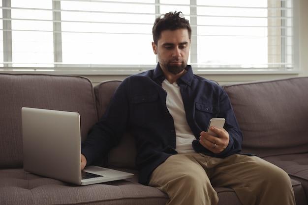 Man met behulp van mobiele telefoon en laptop op de bank Gratis Foto