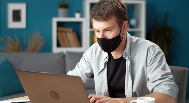 Man met beschermend gezichtsmasker werkt op laptopcomputer thuis blijven tijdens virusuitbraak Premium Foto