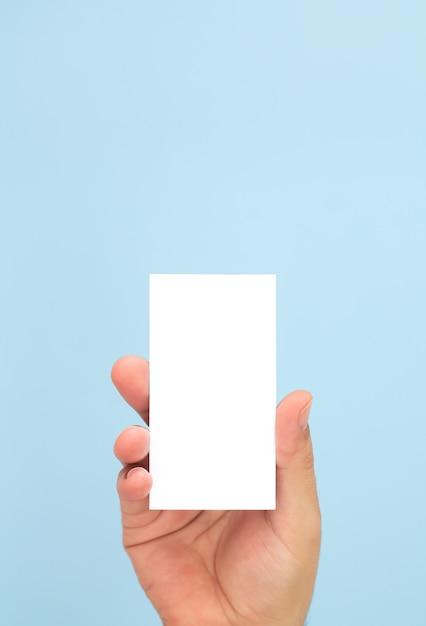 Man met blanco visitekaartje op lichtblauwe achtergrond Premium Foto
