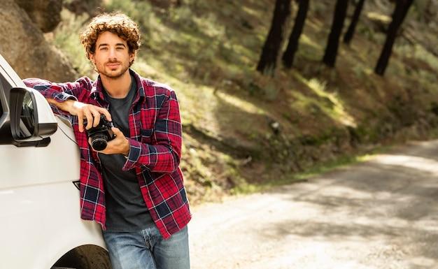 Man met camera en leunend op auto tijdens een road trip Premium Foto
