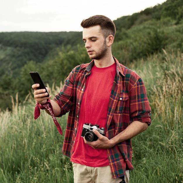 Man met camera en mobiel Gratis Foto
