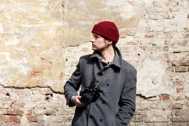 Man met camera staat voor verwoeste muur Gratis Foto