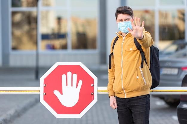 Man met chirurgische masker met stopbord Gratis Foto