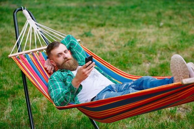 Man met een app op zijn mobiele telefoon wit swingend in een hangmat Premium Foto