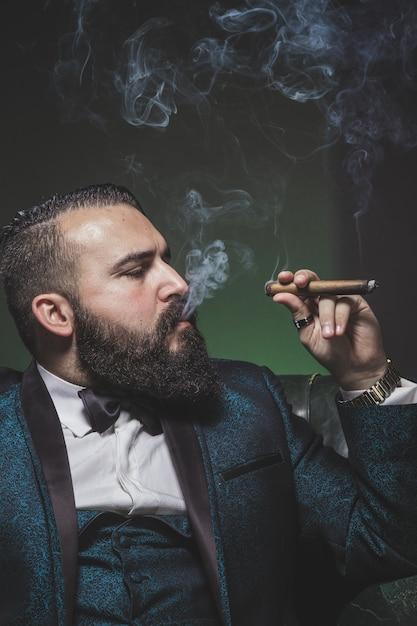 Man met een baard en een groen pak, sigaren roken en roken in profiel. Premium Foto