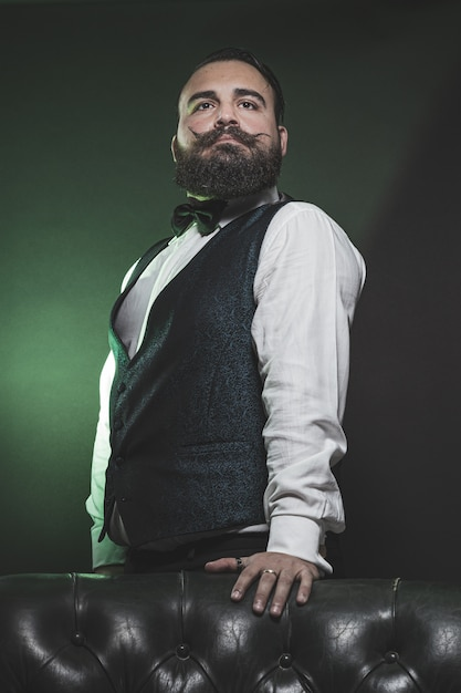 Man met een baard, gekleed in een vest en vlinderdas, staande op een bank. Premium Foto