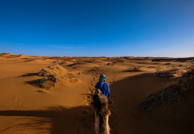 Man met een blauw shirt lopen voor een kameel in het midden van zandduinen met heldere hemel Gratis Foto