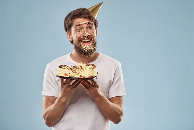 Man met een bord met cake in een feestmuts Premium Foto