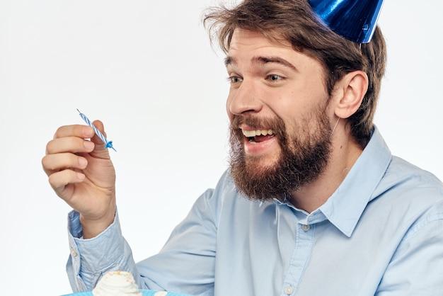 Man met een cupcake en een kaars in een feestmuts Premium Foto