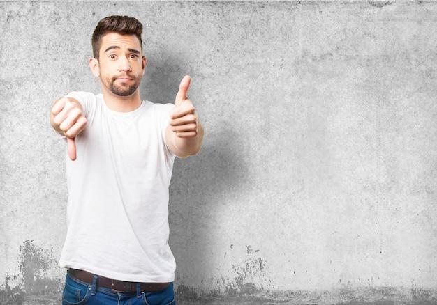 Man met een duim omhoog en één naar beneden Gratis Foto