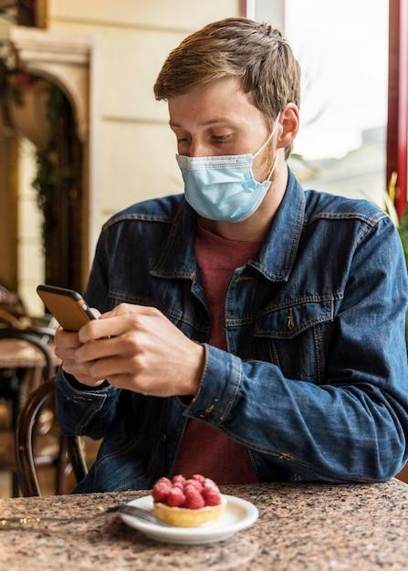 Man met een gezichtsmasker tijdens het controleren van zijn telefoon Gratis Foto