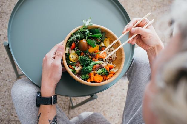 Man met een gezonde levensstijl en groene voedselkeuzes eet verse en heerlijke buddha bowl-schotel met voedingsstoffen en eiwitten Gratis Foto