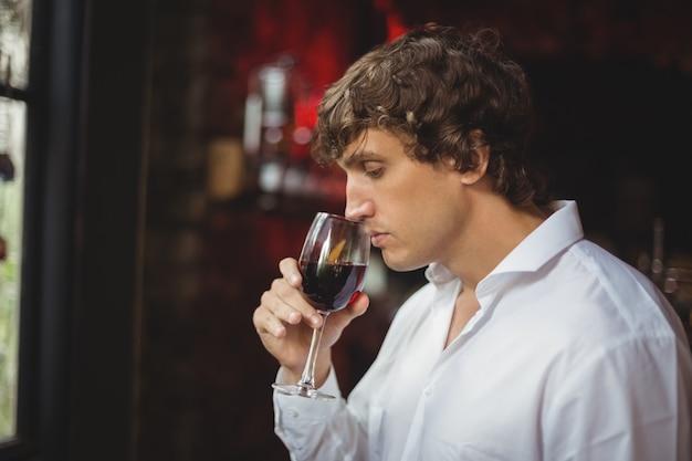 Man met een glas rode wijn Gratis Foto