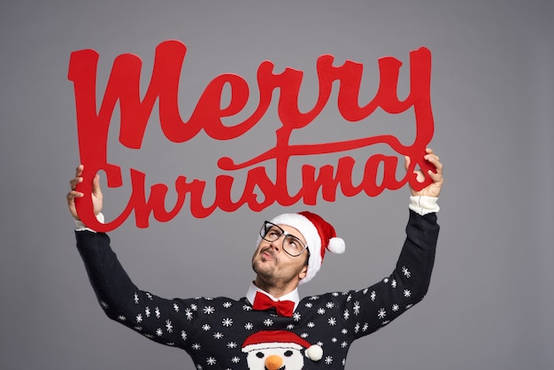 Man met een groot bord met merry christmas Gratis Foto