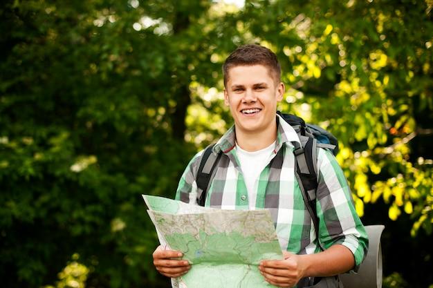 Man met een kaart in het bos Gratis Foto