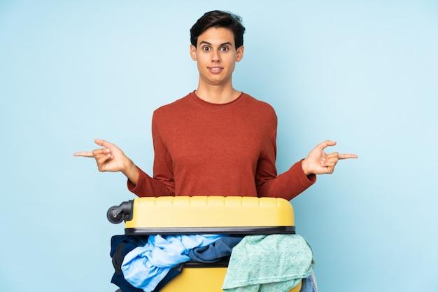 Man met een koffer vol kleren over blauwe muur die naar de zijkanten wijst die twijfels hebben Premium Foto