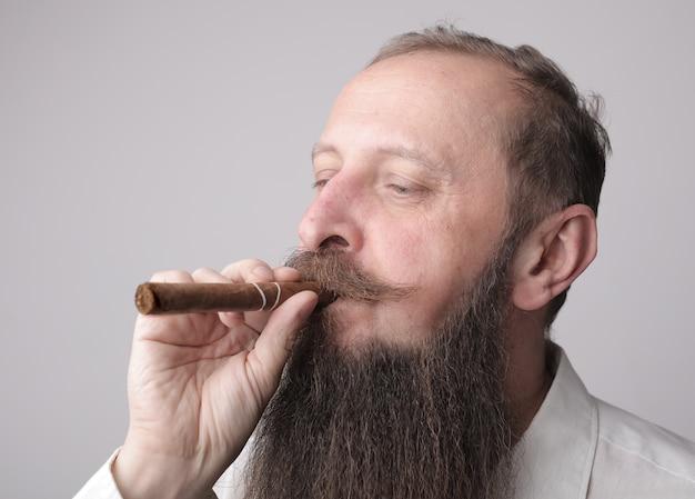 Man met een lange baard en een snor die een sigaar rookt met een grijze muur Gratis Foto