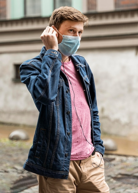 Man met een medisch masker buiten Gratis Foto