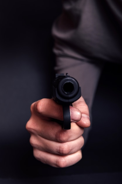 Man met een pistool klaar om te schieten, focus op het wapen. Premium Foto