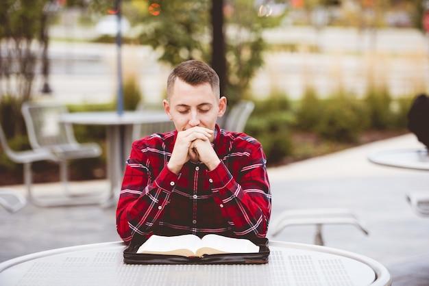 Man met een rood shirt zittend aan een tafel met n open boek in de vorm van hem Gratis Foto