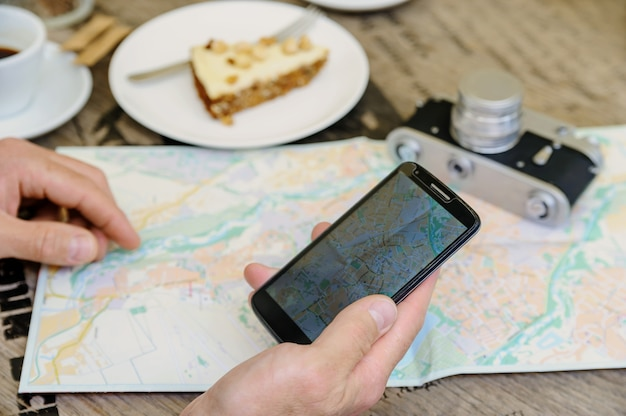 Man met een smartphone daar vlakbij, een vintage camera, een kaart, een kopje koffie en een cake Premium Foto
