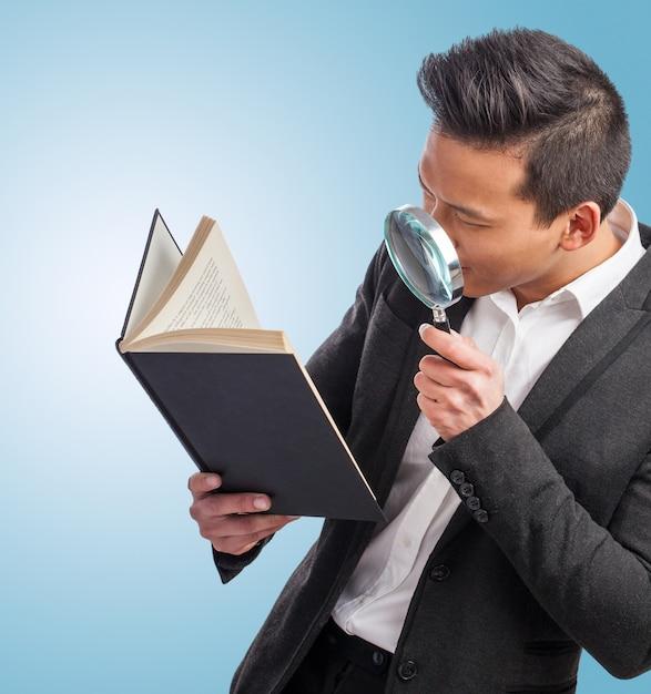 Man met een vergroot glas op zoek naar een boek Gratis Foto