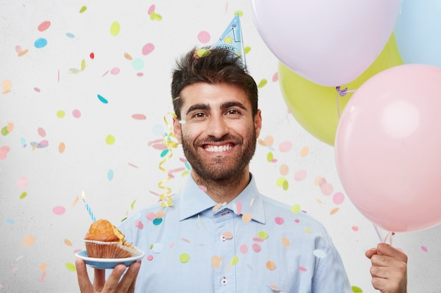 Man met feestmuts en confetti Gratis Foto