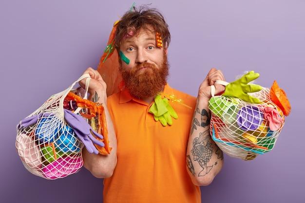 Man met gemberbaard met zakken met plastic afval Gratis Foto