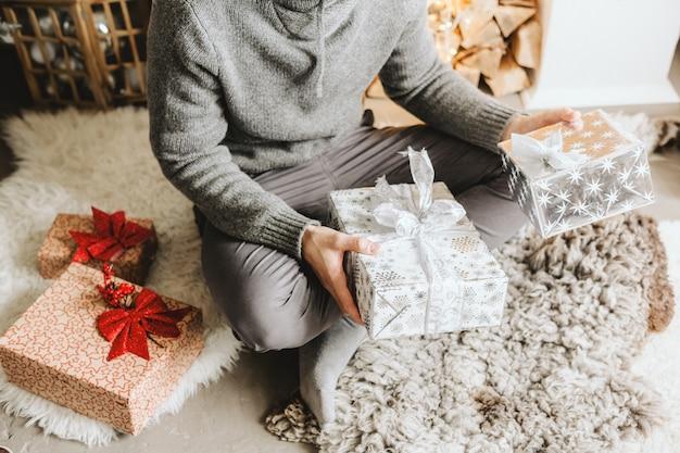 Man met geschenken thuis voor kerstmis Premium Foto