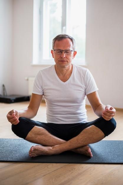 Man met gesloten ogen het beoefenen van yoga Gratis Foto