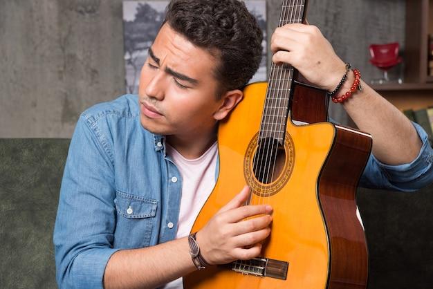 Man met gesloten ogen met een mooie gitaar en zittend op de bank. hoge kwaliteit foto Gratis Foto