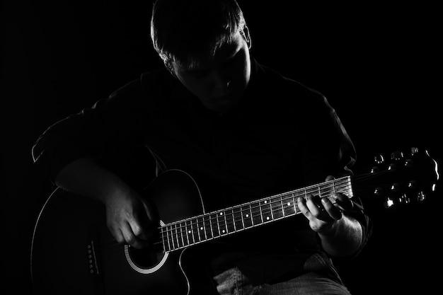 Man met gitaar in duisternis Gratis Foto