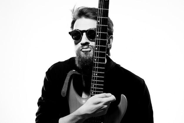 Man met gitaar in handen muzikant rockster prestaties levensstijl licht Premium Foto