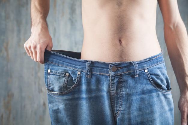 Man met grote maten jeans. gewichtsverlies Premium Foto