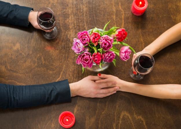 Man met handen met vrouw aan tafel met glazen en bloemen Gratis Foto