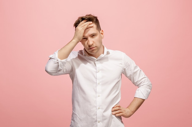 Man met hoofdpijn. geïsoleerd over roze muur. Gratis Foto
