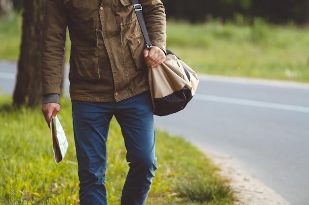 Man met kaart en tas in de hand lopen langs de weg Premium Foto