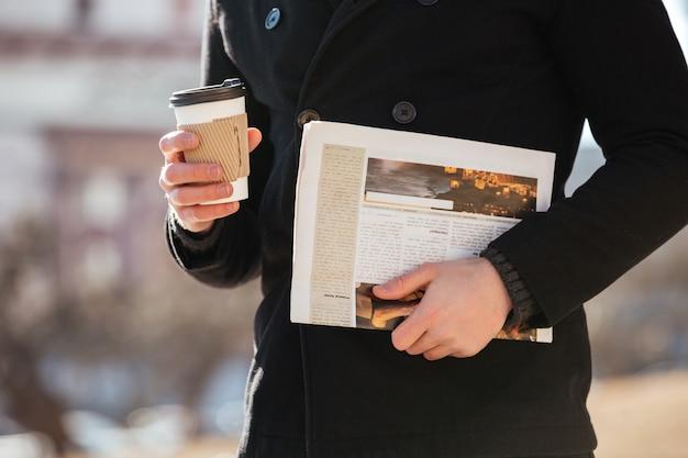 Man met koffie en krant wandelen in de stad Gratis Foto