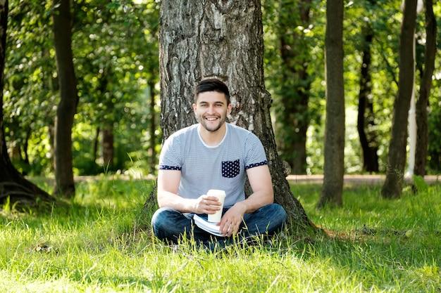 Man met koffie in het park Premium Foto