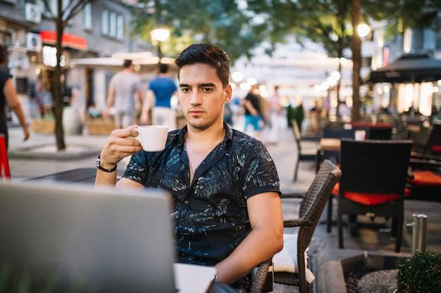 Man met kopje koffie kijken naar laptop scherm Gratis Foto
