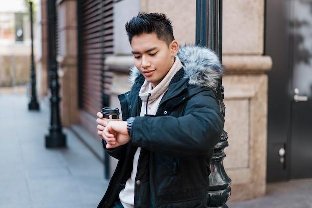 Man met kopje koffie op zoek naar zijn horloge Gratis Foto