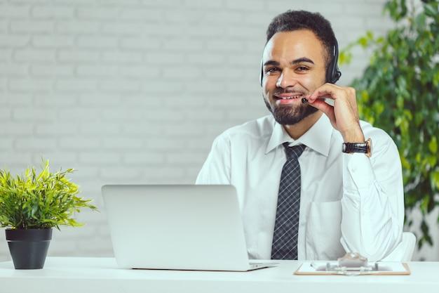 Man met koptelefoon. call centreexploitant die met cliënt spreekt Premium Foto